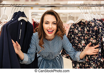 Happy young lady standing in clothes shop - Photo of happy...