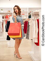 Woman using smartphone while looking through clothes - Young...
