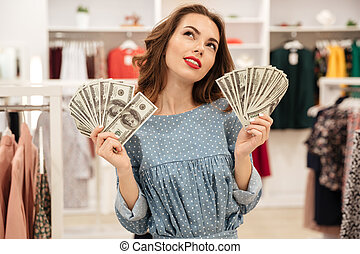 Woman with fans of money dreaming - Young pretty woman with...