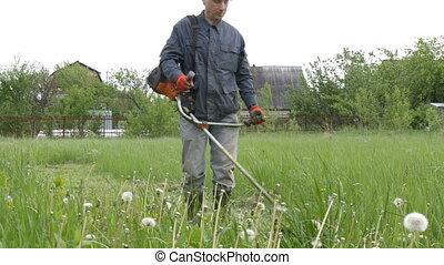 A man mows the grass near his country house. - A man mows...