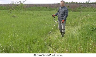 Slow Motion : A man mowing the grass in the garden in summer...