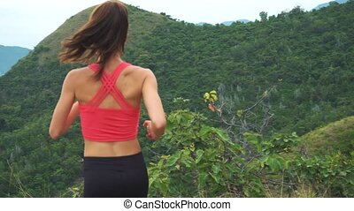 Woman runner happy and celebrating success. Female run on top of the mountain, cheering in winning gesture, victoriously outstretching arms up. Freedom.