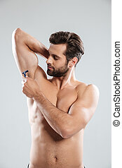 Portrait of a young bearded man shaving his armpit isolated...