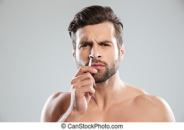 Confused man trying to tweezer hair in nose - Confused...
