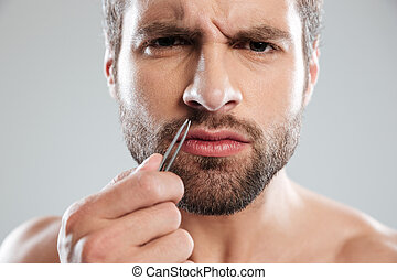 Man holding tweezer and frowning - Young bearded man...