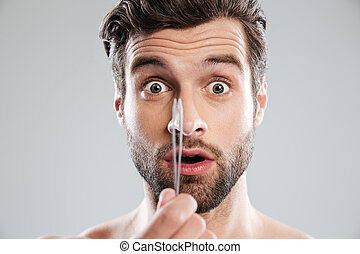 Shocked man with tweezer looked camera - Shocked young man...