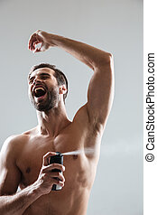 Happy man using deodorant with pleasure isoated
