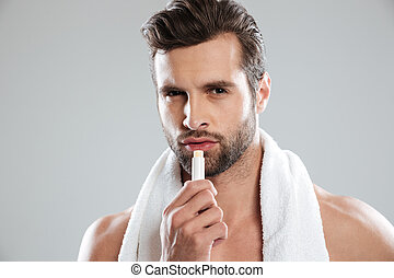 Man looking camera and using lipstick - Man with towel...