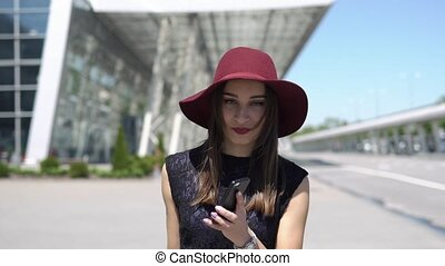 Woman in red hat talks on the phone