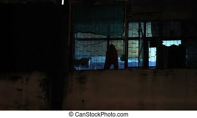 Night in slum area in Bangkok. Window with working...
