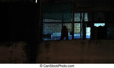 Night in slum area in Bangkok. Window with working...