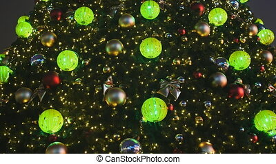 Decorated Christmas tree in toys for Christmas in Moscow on the street. Glowing golden balls and garlands on the branches. New Year theme.