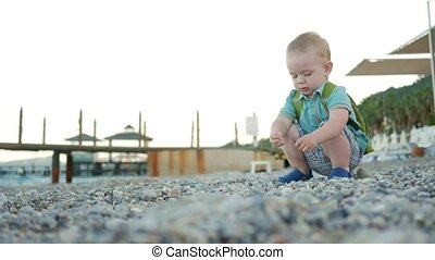A cute kid plays alone by the sea. He carefully touches and...