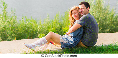 couple in love sitting near the summer lake shore