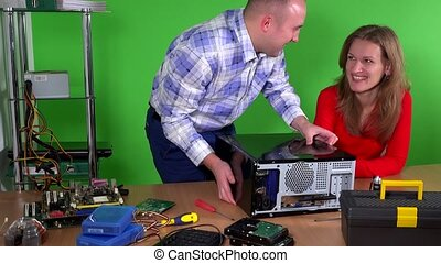 Man repairing computer of his colleague office girl....