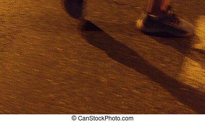 Evening male runner's feet close-up steadicam shot. 4K video...