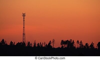 Silhouette of a cell tower against orange sunset sky. 4K...