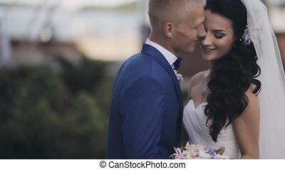 Happy newlyweds hugs outside in nature. Beautiful groom and...