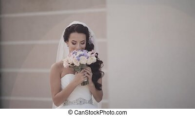 Beautiful brunette bride holding the bouquet. Woman in...