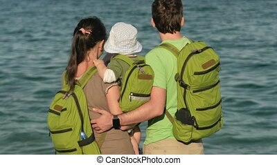 Young family with a baby looking at the sea and hugging....
