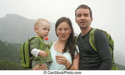 A young family of travelers with a toddler are watching the camera near the beautiful mountains. Everyone is smiling and playing with his son.