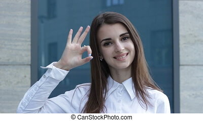 business Lady shows OK gesture and smiles - young business...