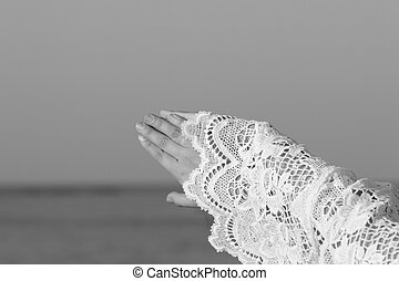 obvernuti hand in a lace against the background of the sea