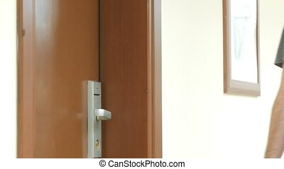 A man opens a hotel room with a card key. - A man opens a...