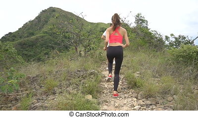 Fit boy and girl jogging on mountain track. Woman and man run in nature