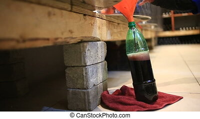 man pours wine into a bottle from a barrel. wine Vault. -...