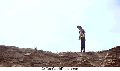 young slim athletic blonde in sports unform posing on a sand hill