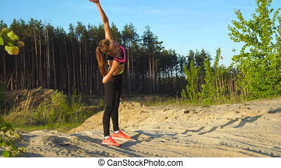 young beautiful slim woman practicing outdoors on a sand