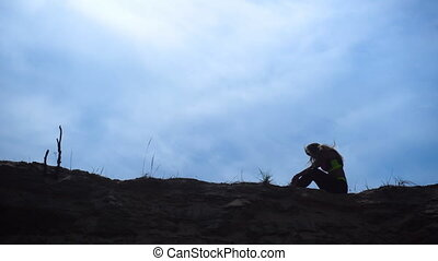 silhouette of young athletic girl on sand hill