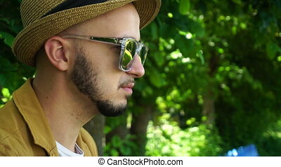 glamour young man in mirror sunglasses drinks coffee in the park