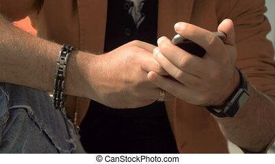 stylish man uses mobile phone - close up of tylish man uses...