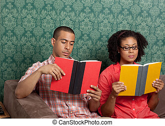 Young couple sitting side by side and reading books at home