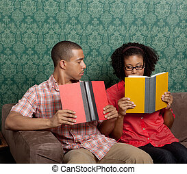 Young African American couple reading books on sofa