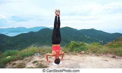 Young woman practicing yoga headstand on top of rock. Landscape mountain view.
