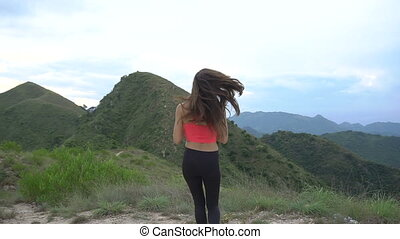 Running woman drink water on mountain road. Sport girl exercising outside in mountains