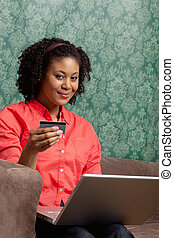 Portrait of a relaxed young woman using a credit card to shop online on couch at home