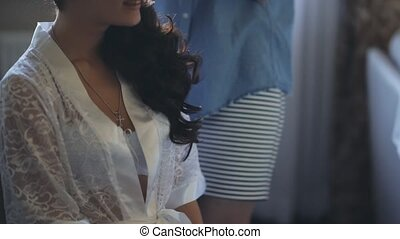 Beautiful brunette woman in white peignoir waiting the hairdresser. Attractive female does a new hairstyle.