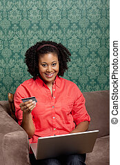 Happy beautiful young female using a credit card to shop online