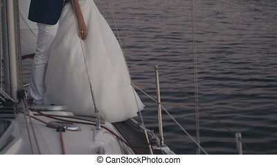 Close-up view of young couple in wedding suits standing on the board of the yacht. Bride and groom hugging in evening.