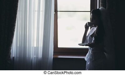 Young bride staying near the window and drinking coffee in...