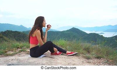 Runner woman eat apple on mountain peak.