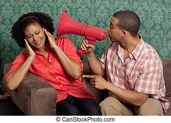 Young man using the megaphone to yell at his girlfriend
