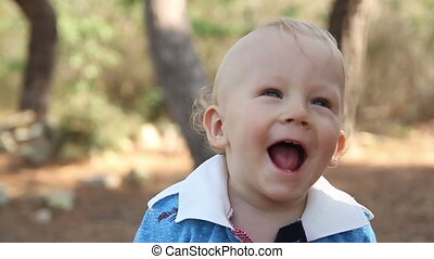 A little boy laughs sincerely in the background of the park.