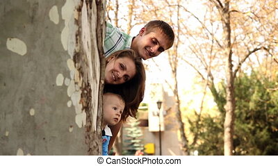 Family looking out from behind tree trunk and smiling -...