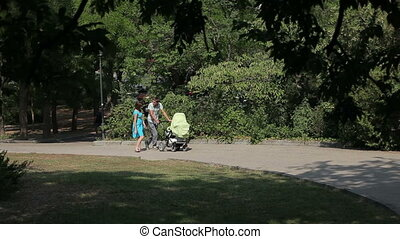 happy parents are walking with their little son in park