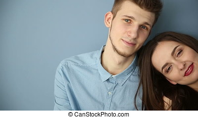 Young couple in love sitting at home by the blue wall